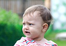 Beautiful sad baby crying on nature Royalty Free Stock Image