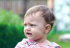 Beautiful sad baby crying on nature Royalty Free Stock Image
