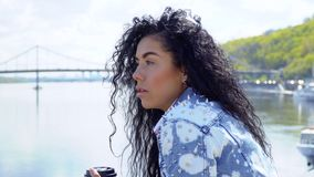 Beautiful sad brunette against blurred river and bridge. Young sad brunette stands at the embankment and thinks about something personal. Upset woman looks at stock footage