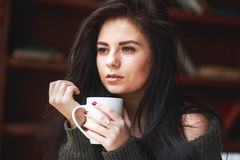 Beautiful sad brunette woman with a cup of coffee or tea. At home . Drinking coffee Stock Photography