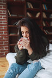 Beautiful sad brunette woman with a cup of coffee or tea. At home . Drinking cofee Royalty Free Stock Photography