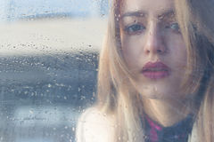 Beautiful sad girl with big eyes in a coat is behind wet glass. Beautiful sad girl with big  eyes in a coat is behind wet glass Royalty Free Stock Photography