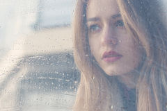 Beautiful sad girl with big eyes in a coat is behind wet glass Royalty Free Stock Photography