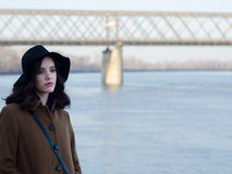 Beautiful sad girl in classic coat and hat beside river Royalty Free Stock Photos