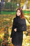 Beautiful sad girl in an elegant black coat on a sunny day in autumn park. Stock Images