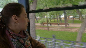 Beautiful sad girl looks through the window of a tram. A beautiful girl with sad eyes rides in a tram. It is raining outside. She`s in a bad mood, she`s sad, bad stock video footage