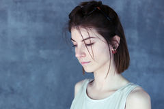 Beautiful sad girl. Lowered her eyes, portrait in profile, blue background Stock Photo