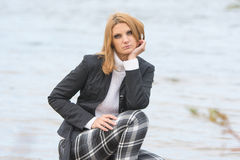 Beautiful sad girl sat by the river in the warm autumn weather Stock Image