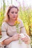 Beautiful sad girl sitting on meadow Stock Photos