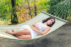 Beautiful sad girl in white dress lying in hammock. In summer forest Royalty Free Stock Image