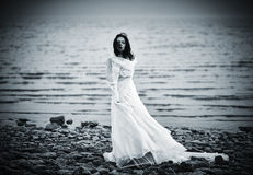 Beautiful sad girl in white dress standing on sea coast Stock Photo