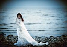 Beautiful sad girl in white dress standing on sea coast Stock Photo