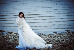 Beautiful sad girl in white dress standing on sea shore Royalty Free Stock Images