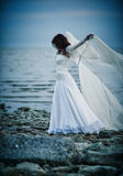 Beautiful sad girl in white dress standing on sea shore Stock Photos