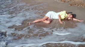 A beautiful, sad girl in a yellow-white dress and long blond hair lying on the sand, with her eyes closed at the. Seashore, is covered with a wave, foam, covers stock video