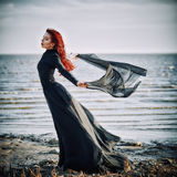 Beautiful sad goth girl with cloth in hands standing on sea shore Royalty Free Stock Images