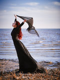 Beautiful sad goth girl with cloth in hands standing on sea shore Stock Photos