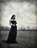 Beautiful sad goth girl stands in autumnal field. Grunge texture effect Stock Image