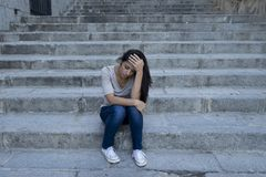 Beautiful and sad Hispanic woman desperate and depressed sitting on urban city street staircase stock image