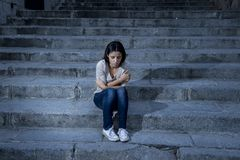 Beautiful and sad Hispanic woman desperate and depressed sitting on urban city street staircase stock images