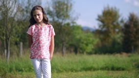 Beautiful sad little girl standing on a nature stock video