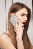 Beautiful, sad, upset girl talking on the phone model, red lips. Professional makeup, hairstyle Royalty Free Stock Photo