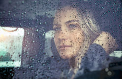 Beautiful sad woman in the car Stock Images