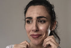 Beautiful and sad woman crying desperate and depressed with tears on her eyes suffering pain. Beautiful face of sad woman crying desperate and depressed with Stock Image