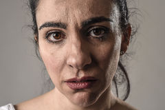 Beautiful and sad woman crying desperate and depressed with tears on her eyes suffering pain. Beautiful face of sad woman crying desperate and depressed with Stock Photography