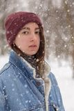 Sad winter woman. Beautiful sad woman relax on winter forest under falling snow royalty free stock image