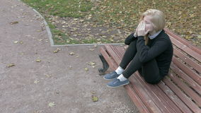 Beautiful sad woman sitting in city park stock footage