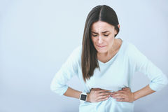 Beautiful sad woman suffering from stomachache. royalty free stock photography