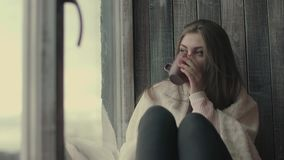 Beautiful sad woman by the window at home. Sad girl near window thinking about something drinks tea stock video