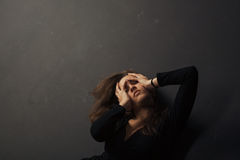 Beautiful sad young woman holding hands on her face on a dark background Stock Photos