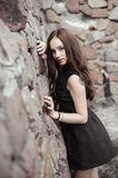 Beautiful sad young woman on a stone wall background Stock Photos