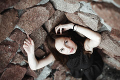 Beautiful sad young woman on a stone wall background Royalty Free Stock Photos
