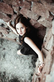 Beautiful sad young woman on a stone wall background Royalty Free Stock Image