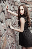Beautiful sad young woman on a stone wall background Stock Images