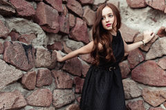 Beautiful sad young woman on a stone wall background Stock Image