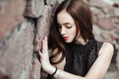 Beautiful sad young woman on a stone wall background Royalty Free Stock Photography