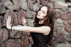 Beautiful sad young woman on a stone wall background Stock Photo