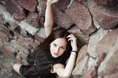 Beautiful sad young woman on a stone wall background. Posing in a black dress, very sensual and emotional Stock Image