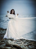 Beautiful sad young woman in white dress standing on sea coast Royalty Free Stock Photography