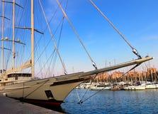 Beautiful sailing ship on the dock port. Beautiful sailboat on the dock port, surrounded by yachts Stock Photos