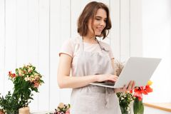 Beautiful sales woman standing near bouquets in flower workshop,. Beautiful sales woman standing near bouquets in flower workshop and using laptop Royalty Free Stock Photography
