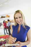Beautiful Saleswoman With Customers In Background Stock Images