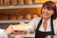 Beautiful saleswoman is selling pastry in bakery Stock Photos
