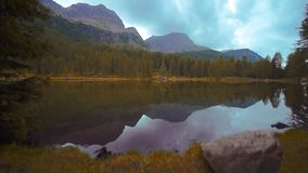 Beautiful San Pellegrino lake that reflects the forest and the mountains in the water stock footage