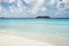 Beautiful sand beach with crystal clear water and cruise ship an Stock Images