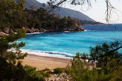 Beautiful sand beach with pine trees and blue sea. With waves at warm sunny summer day. Mediterranean sea, Turkey Stock Photos